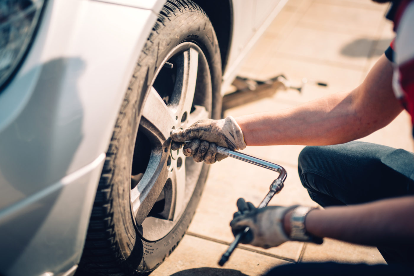 Tire maintenance, damaged car tyre or changing seasonal tires using wrench. Changing a flat car tire on the sideroad